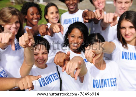 portrait of a happy and diverse volunteer group pointing towards camera - stock photo