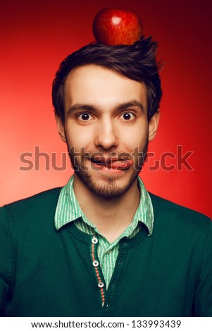Portrait of a happy and mad student guy posing over red background with red apple on head. Education concept. Hipster style. Perfect hairdo. Studio shot