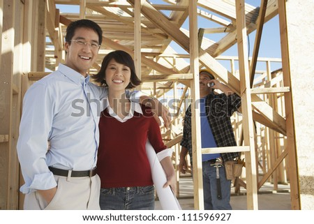 Portrait of a happy Asian couple at construction site with contractor in background