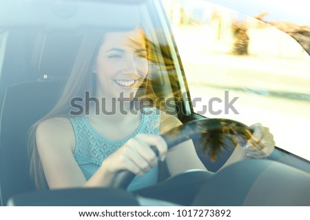 Portrait of a happy attentive driver woman driving a car on the road #1017273892