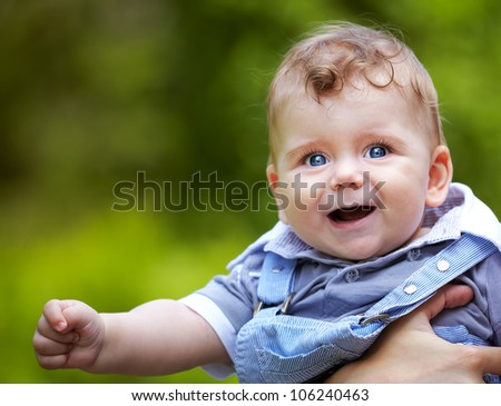 Portrait of a happy baby boy portrait outdoor in summer.