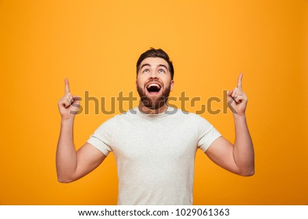 Portrait of a happy bearded man pointing fingers up at copyspace isolated over yellow background