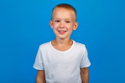 Portrait of a happy beautiful boy in a white t-shirt looking at the camera, isolated in blue on the background