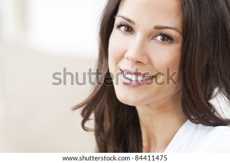 Portrait of a happy beautiful brunette young woman with perfect teeth & smile