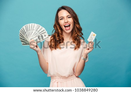 Portrait of a happy beautiful girl wearing dress holding money banknotes and credit card isolated over blue background