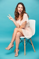 Portrait of a happy beautiful girl wearing dress sitting on a chair and winking isolated over blue background