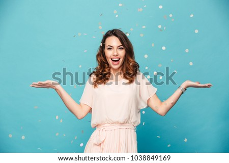 Portrait of a happy beautiful girl wearing dress standing standing under confetti rain and celebrating isolated over blue background