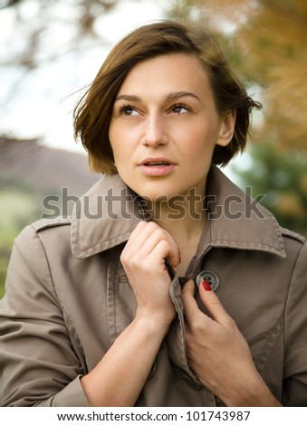 Portrait of a happy beautiful woman in autumn park, pale colors
