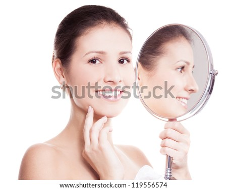 portrait of a happy beautiful woman looking into the mirror, isolated against white background