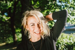 Portrait of a happy blonde woman, walking in park, laughing and looking at camera