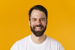 Portrait of a happy brunette bearded man standing over yellow wall, laughing