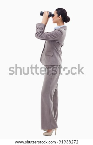 Portrait of a happy businesswoman looking through binoculars against a white background