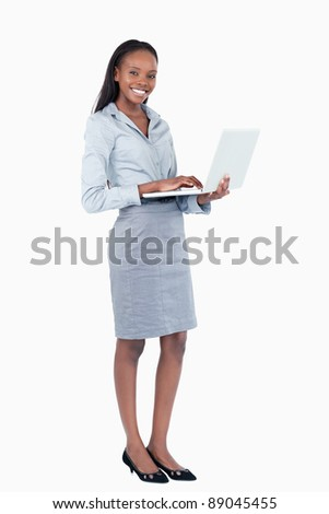 Portrait of a happy businesswoman using a laptop while standing up against a white background