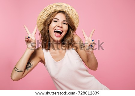 Portrait of a happy cheerful girl in summer hat showing peace gesture with two hands isolated over pink background