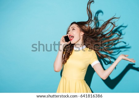 Portrait of a happy cheerful girl with long beautiful hair wearing dress and talking on mobile phone isolated over blue background #641816386