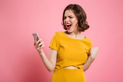 Portrait of a happy cheerful woman celebrating success while standing and looking at mobile phone isolated over pink background