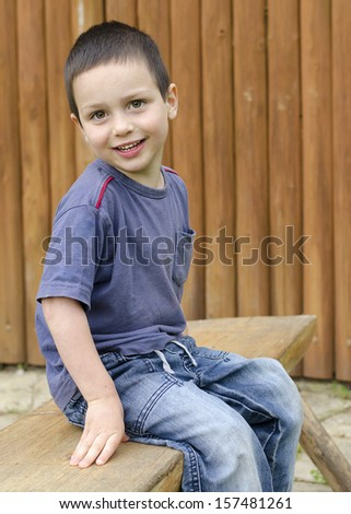 Portrait of a happy child boy sitting on a wooden bench.