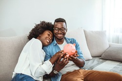 Portrait of a happy couple at home saving money in a piggybank. Portrait of a happy African American couple at home saving money in a piggybank and smiling