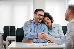 Portrait of a happy couple handshake with investment adviser.