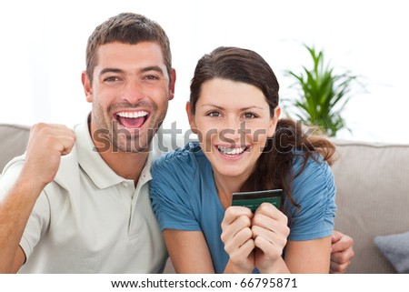 Portrait of a happy couple holding their credit card on the sofa at home