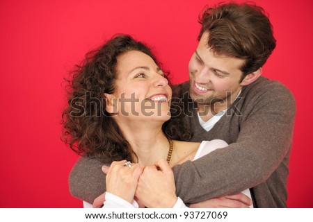 portrait of a happy couple hugging on red background