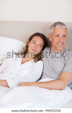 Portrait of a happy couple lying on a bed while looking away from the camera