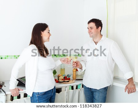 Portrait of a happy couple preparing food and drinking white wine