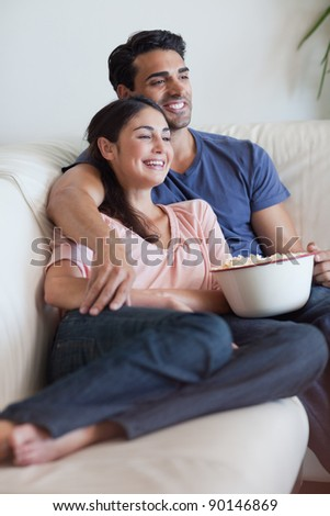 Portrait of a happy couple watching television while eating popcorn in their living room