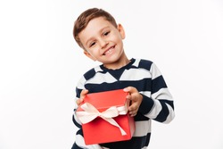 Portrait of a happy cute little kid holding gift box and looking at camera isolated over white background