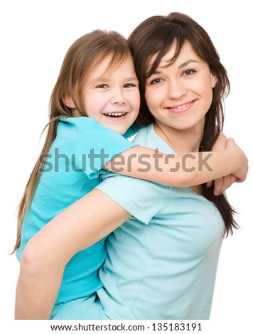 Portrait of a happy daughter piggyback ride her mother, isolated over white - stock photo