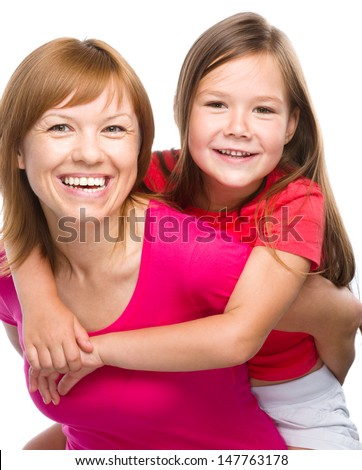 Portrait of a happy daughter piggyback ride her mother, isolated over white