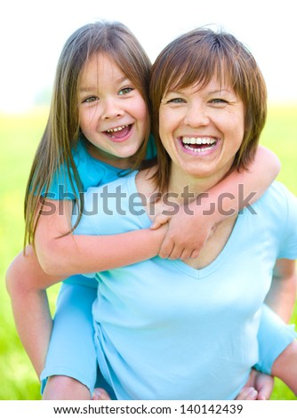 Portrait of a happy daughter piggyback ride her mother, outdoor shoot - stock photo