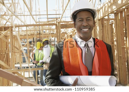 Portrait of a happy engineer holding blueprint at construction site