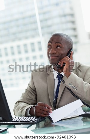 Portrait of a happy entrepreneur making a phone call while reading a document in his office