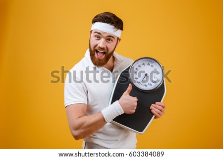 Portrait of a happy excited bearded fitness man holding weight scales and showing thumbs up isolated on orange background