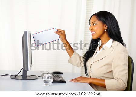Portrait of a happy executive woman at work sending the mail through the computer