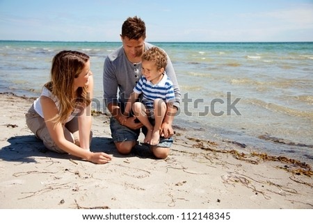 Portrait of a happy family enjoying their summer vacation on the beach
