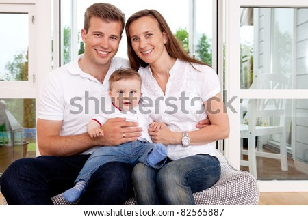 Portrait of a happy family looking at the camera in a home interior
