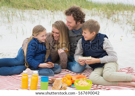 Portrait of a happy family of four enjoying picnic at the beach