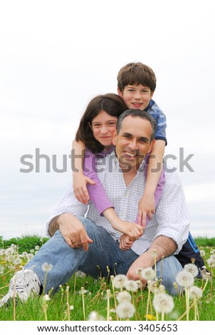 Portrait of a happy family of three on green grass