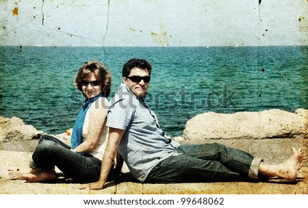 portrait of a happy family on the background of the sea. Photo in old image style.