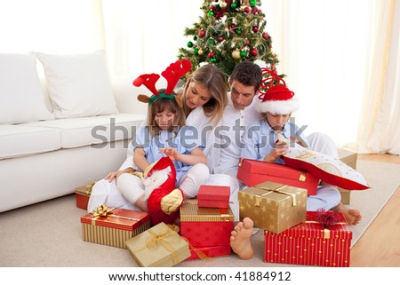 Portrait of a happy family opening gifts at Christams time