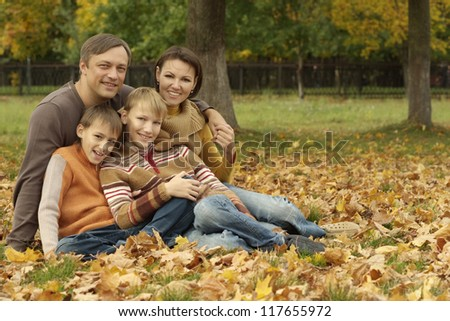 portrait of a happy family sitting in a beautiful autumn park