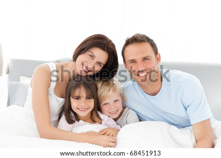 Portrait of a happy family sitting on the bed in the morning