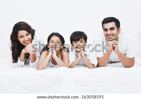Portrait of a happy family smiling on the bed