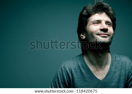 Portrait of a happy fashionable handsome man in gray sweater (pullover) over blue (green) background with a friendly smile. Close-up. Copy-space. studio shot