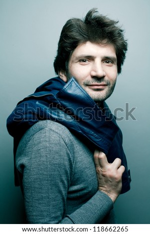 Portrait of a happy fashionable handsome man in gray sweater (pullover) with blue leather jacket on his shoulders over blue (green) background with a friendly smile. studio shot