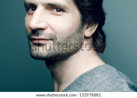 Portrait of a happy fashionable handsome mature man in gray sweater (pullover) posing over dark blue (green) background with a friendly smile. Perfect hair and skin. Close up. Studio shot