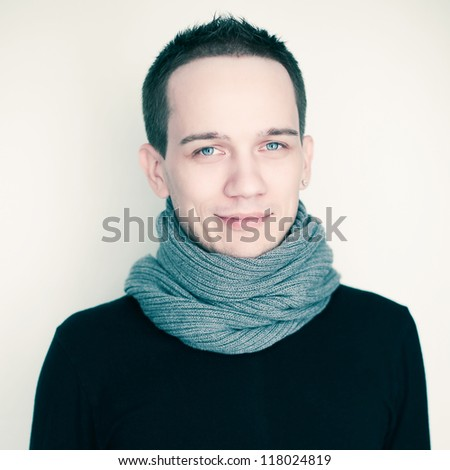 Portrait of a happy fashionable male model in black sweater and gray scarf over white background. Studio shot