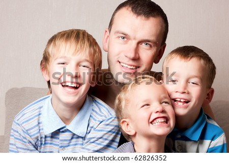 Portrait of a happy father with sons, indoor.